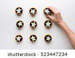 the hand puts star shaped tarts ...   Shutterstock . vector #523447234