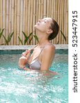 young woman relaxing in the pool | Shutterstock . vector #523447915