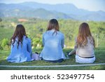 Three young women viewed from behind while wearing casual dress and sit on green grass in garden.