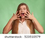 Small photo of Surprise. Woman portrait, fingers near face spread. Mouth open, eyes wide. Isolated on green. Surprise. Emotion - wonder, joy, astonishment, amazement, fear, delight.