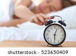 young sleeping woman and alarm... | Shutterstock . vector #523650409