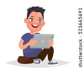 boy holding a tablet in hands.... | Shutterstock .eps vector #523665691