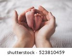 Small photo of Parent holding in the hands feet of newborn baby.