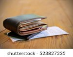 Stock photo soft tone of money and credit card in a leather wallet on wooden table and bill slip background 523827235
