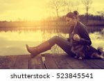 woman with dog in sunset | Shutterstock . vector #523845541