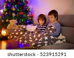 Small photo of Two sweet children, boy brothers, playing on phone under the blanket on first advent Sunday, christmas tree behind them