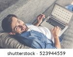 handsome man is using a laptop  ... | Shutterstock . vector #523944559