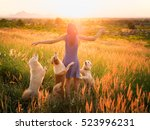 Stock photo trendy girl in stylish summer dress with dog friend walking in the field with flowers in sunlight 523996231