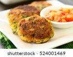 Small photo of Zucchini, couscous and parsley fritters with tomato and onion dip on the side, photographed with natural light (Selective Focus, Focus in the middle of the first fritter)