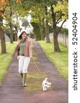 Stock photo woman taking dog for walk outdoors in autumn park 52404904