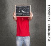 Small photo of Man holding a blackboard with stop racism, discrimination and social exclusion message written on it
