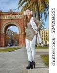 Small photo of in Barcelona for a perfect winter. Full length portrait of young fashion-monger in earmuffs near Arc de Triomf in Barcelona, Spain looking into the distance