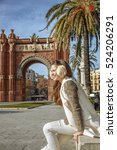 Small photo of in Barcelona for a perfect winter. happy elegant fashion-monger in earmuffs near Arc de Triomf in Barcelona, Spain sitting on a parapet