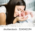 mother kissing infant feet | Shutterstock . vector #524342194