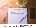 Small photo of Office desk with a paper written Reference with pen, glass, smartphone and a thumb drive