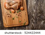 Raw chicken drumstick on a wooden board with salt, garlic, rosemary, spices. - stock photo