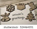 Small photo of closeup of a piece of paper with the text text seasons greetings written in it and some christmas ornaments, on a rustic wooden surface