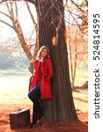 Small photo of Beautiful young woman with vintage suitcase in a autumn park. She is leaning against a tree.
