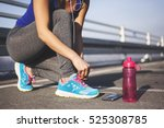 Small photo of Female runner tying her shoes preparing for a jog