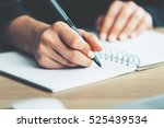 Stock photo close up of woman s hands writing in spiral notepad placed on wooden desktop with various items 525439534