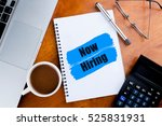 """Small photo of """"Now Hiring"""" words on notebook with a cup of coffee, pen, calculator, spectacles, and a a laptop - jobs and business concept"""