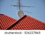 Small photo of TV antennas and satellite dish for television mounted on the tiled roof of house isolated on blue sky background in countryside. Telecommunications aerials and receiver devices on rooftop of building
