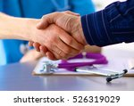 Small photo of doctor with stethoscope on the patient's admission at the table