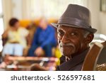 Stock photo portrait of elderly black man looking at camera in retirement home with group of friends in 526597681