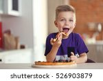 cute boy eating pizza at home | Shutterstock . vector #526903879