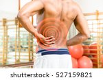 Small photo of Man body with aching back rear view with red circles expressing pain and fitness center background - Shirtless african guy touching his painful hip inside gym - Medical concept of workout risks
