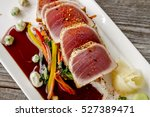 Small photo of Close up of rare seared Ahi tuna slices with bok choy stir fry vegetables and wasabi peas on white plate from above