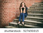 Smiling Young Woman Sits On...