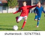 boys kicking football on the... | Shutterstock . vector #527677561