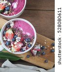Small photo of acai berry smoothie bowls on wooden background.