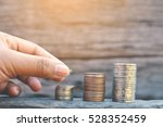 hand holding coin on old wood... | Shutterstock . vector #528352459