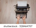 Small photo of typewriter, vintage black with a sheet of clean white paper and children's hands typing on the keys against the light wood