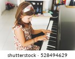little girl playing piano at... | Shutterstock . vector #528494629