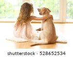 Stock photo little girl with golden labrador dog in room 528652534