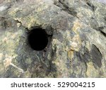 Small photo of Dark hole drilled in rock. This is the type of hole dynamite is put in to blast rocks and cliffs. The rock is mostly dark green. Focus is on the top edge of the hole. Room for text on the right.