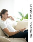 Small photo of Young handsome brunette man relaxed with a phone in hand, free online dating, gigolo, adult applications, benefits and risks with smartphone usage, communicating with friends, family, and coworkers