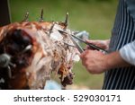 Small photo of hog roast being carved for serving
