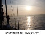 Girl standing on boat before bridge at sunrise - stock photo
