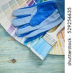 Small photo of Collection of protective gloves color sampler paintbrushes on wooden board construction concept.
