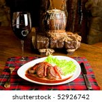 Roast maral meat with blood and garnish pearl barley at table with wine - stock photo