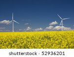 rapeseed field and wind turbines - stock photo