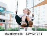 Happy Girl Swinging Outdoors O...
