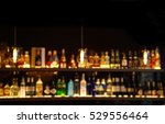 Stock photo blur alcohol drink on bar counter in the dark night background 529556464