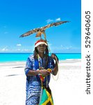 Small photo of Cuba, Varadero - 09 April, 2016: a cool rastaman holding a tamed eagle on the beach of Varadero, Cuba, with the Atlantic Ocean in the background