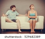 Small photo of Bad relationship concept. Man and woman in disagreement. Young couple sitting on couch at home having quarrel, offended wife and unhappy husband