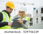 builders in hardhat with tablet ... | Shutterstock . vector #529746139